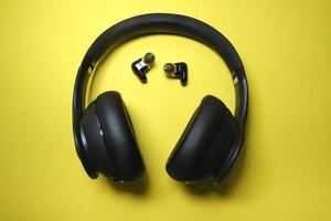 Black headphone and tiny earbuds on yellow background photo