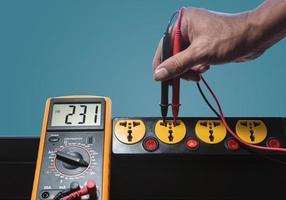 medir el voltaje de CA de la toma de corriente con un medidor digital foto