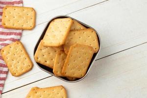 galletas saladas en un recipiente de acero inoxidable con mantel foto