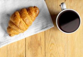 Croissant on white fabric with coffee on wooden table photo