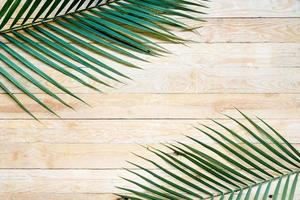 Flat lay palm leaf on wooden table and tree frame with copy space photo