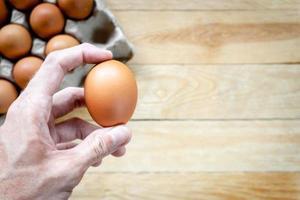 Hombre sujetando huevo de gallina fresco con espacio de copia foto