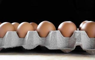 Huevos en paquete sobre mesa con fondo negro foto