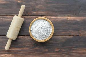 Rolling pin and flour in bowl on wooden table photo