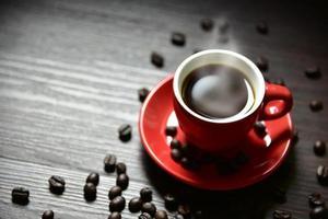 Taza de café roja con vapor de corriente y granos de café. foto