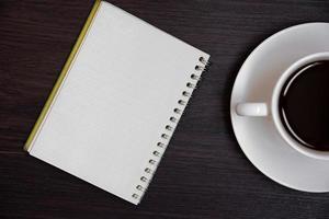 vista superior de la taza de café y el cuaderno en blanco para memo foto