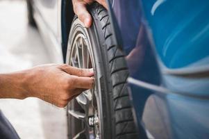 Closeup male automotive technician removing tire valve nitrogen cap photo
