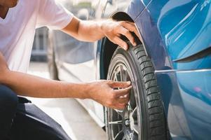Closeup male automotive technician removing tire valve photo