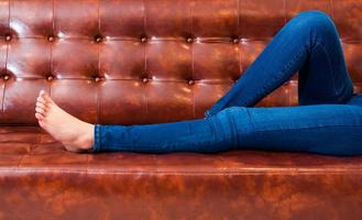 Woman legs with wearing jeans while relaxing at movie theater photo