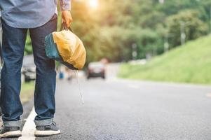 Closeup of tourist legs walking along road with bag during travel photo