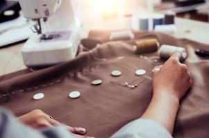 Dressmaker designing new fashion dress sewing machine photo