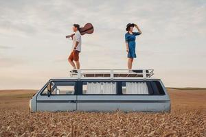 man with a guitar and woman are standing on roof of a car in a wheat photo