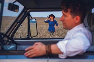 man driving car and woman in dress and hat walking through wheat field photo