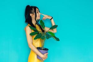 Bella mujer tiene flor en maceta sobre un fondo azul. foto