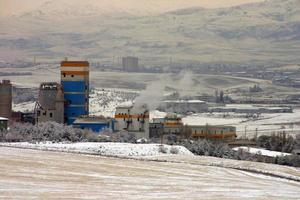 paisaje nevado, una fábrica de cemento y una zona industrial. foto