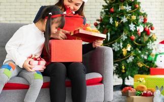 madre e hijo asiáticos abren juntos la caja de regalo de navidad foto