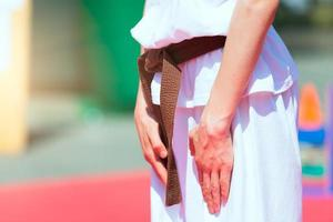 Detalle de un niño con cinturón de karate marrón foto