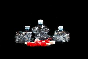 Transparent plastic bottles crushed and plugs on a black background. photo