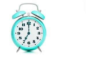 Classic table alarm clock in green color on a white background photo