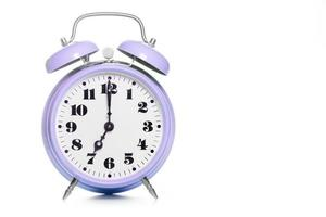 Clásico reloj despertador de mesa púrpura sobre un fondo blanco. foto