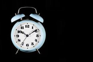 reloj despertador de mesa clásico en color azul claro sobre un fondo negro foto