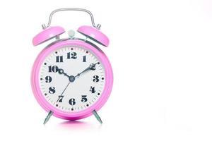 Reloj despertador de mesa rosa clásico sobre un fondo blanco. foto