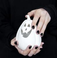 Female hands holding funny pumpkins on black background photo