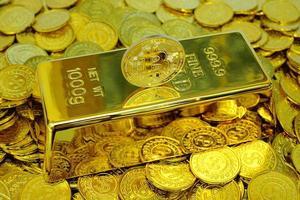 Criptomoneda bitcoin en la barra de oro y pila de monedas de oro. foto