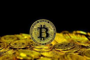 Criptomoneda bitcoin de oro en la pila de monedas de oro en fondo negro foto