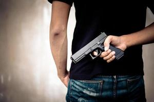 ladrón esconde una pistola en la espalda foto