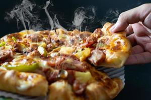 Hand picking sliced pizza with cheese ham bacon and pepperoni photo
