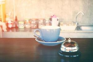 Campana y taza de café caliente en el mostrador de la cafetería. foto