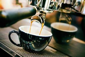 Coffee machine preparing fresh coffee in cup photo