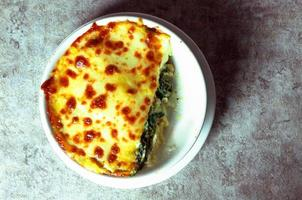 Spinach lasagna with cheese in white plateasagna photo