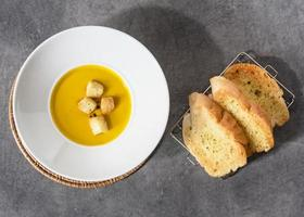Pumpkin soup with croutons bread in plate garlic bread photo