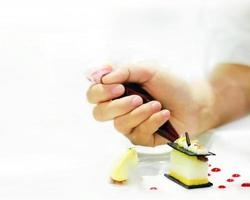 Pastry chef hand with decorating cake photo