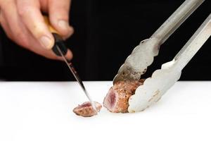 Chef cortando carne asada a bordo en la cocina foto