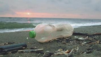 garrafa de plástico descartada na costa arenosa perto do mar ondulante ao pôr do sol video