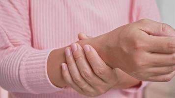 Primer plano de una mujer sosteniendo su muñeca dolorosa causada por un trabajo prolongado. video