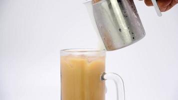 Pour the frothed cream and fresh milk into an iced coffee mug. video