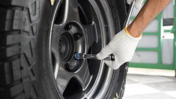 Human hand wearing white gloves tighten the wheel nuts with a wrench. video