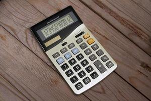 Electronic calculator on wooden background photo