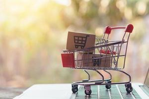 Concepto de compras en línea: paquetes o cajas de papel con un carrito de compras foto