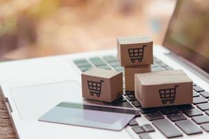Online shopping - Paper cartons or parcel with a shopping cart logo photo