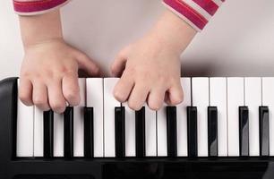 manos de niños pequeños tocando el piano vista superior, concepto de educación foto