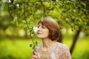 Happy woman inhales aroma of a flower photo