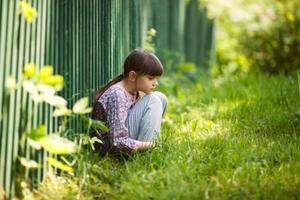Sad girl sitting on the grass photo