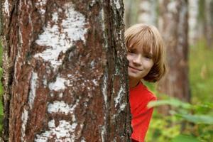 niño asoma desde detrás de un tronco de árbol foto