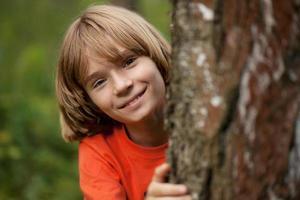 niño en camiseta roja asoma desde detrás de un tronco de árbol foto