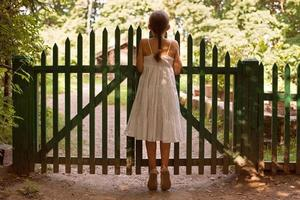 Girl standing on tiptoes and looking over the fence photo
